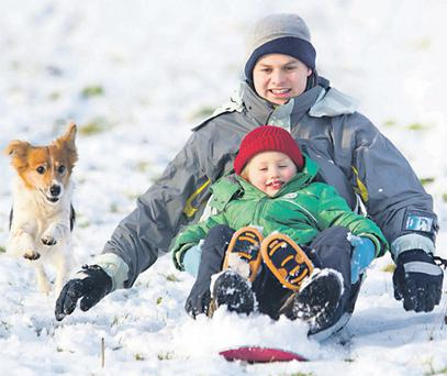 Andy and Luke Griffith (3) and their dog Mook slide down a snow-covered hill in Thomastown, Co Kilkenny, yesterday