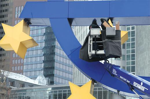 Workmen carry out repairs to the euro sign sculpture outside the European Central Bank (ECB) headquarters in Frankfurt yesterday. Photo: Bloomberg News