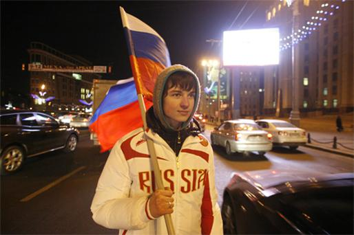 A young football fan holding a Russian flag hands out free national flags to motorists in downtown Moscow, to celebrate FIFA's selection of Russia as host to the 2018 World Cup