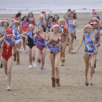 Finalists of the Miss Great Britain beauty pageant run on the beach beside Weston-super-Mare Pier