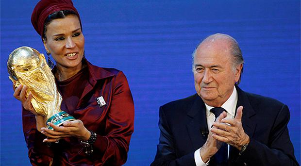Sheikha Moza Bint Nasser al-Missned, wife of Qatar's Emir Sheikh Hamad bin Khalifa Al-Thani, proudly presents a copy of the World Cup received from FIFA President Sepp Blatter. Photo: Reuters