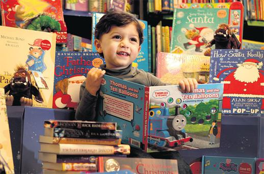 GENTLE RHYMES AND VIVID CHARACTERS: Ahmed Kilinc, 3, pictured with a selection of seasonal books in the children's section of Waterstones bookstore on Dawson Street. Relatively inexpensive, books make an ideal present for children as they provide hours of pleasure. Photo: Gerry Mooney