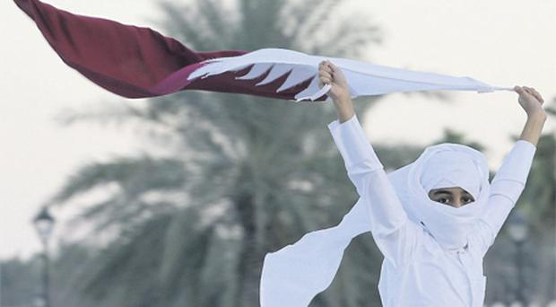 A Qatari man holds the national flag during a celebration in Doha, Qatar, on Friday