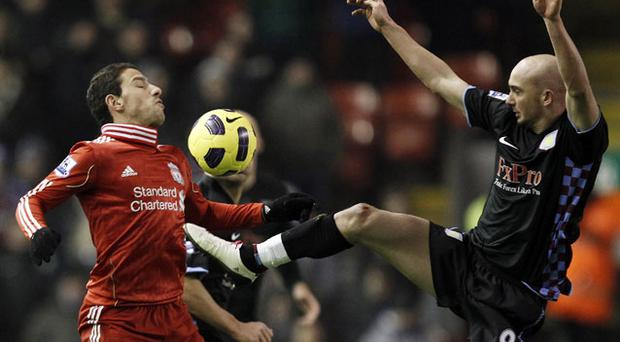 Liverpool's Maxi Rodriguez is challenged by Aston Villa's Stephen Ireland at Anfield last night. Photo: Reuters
