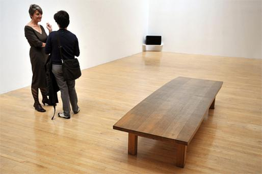 Two women stand and talk amongst Susan Philipsz's artwork, 'Lowlands', which won the Turner Prize last night