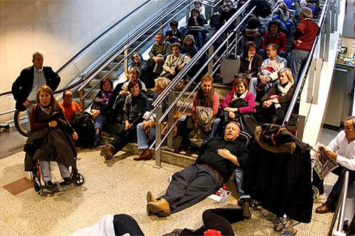Stranded passengers wait in Madrid's Barajas airport after flights were cancelled due to a walkout of air traffic controllers