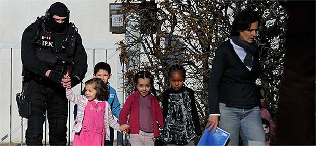Special French intervention police forces (GIGN) and children leaving the Charles Fourier nursery school in Besancon, eastern France