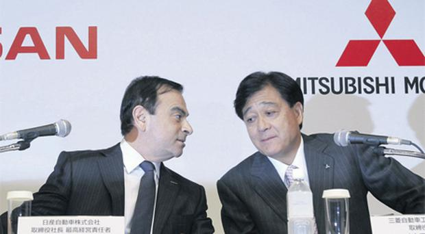Nissan chief executive Carlos Ghosn (left) and Mitsubishi president Osamu Masuko at their joint news conference in Tokyo yesterday