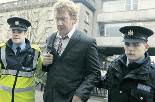 Kevin Galvin is escorted from the High Court by two gardai yesterday after he was jailed for six weeks for contempt of court