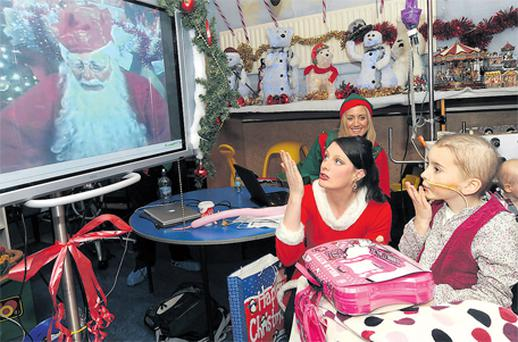 At Our Lady's Children's Hospital in Crumlin, Dublin, Ella Sherlock (right) and Clara Mason, dressed as Mrs Claus, blow a kiss to Santa in the North Pole