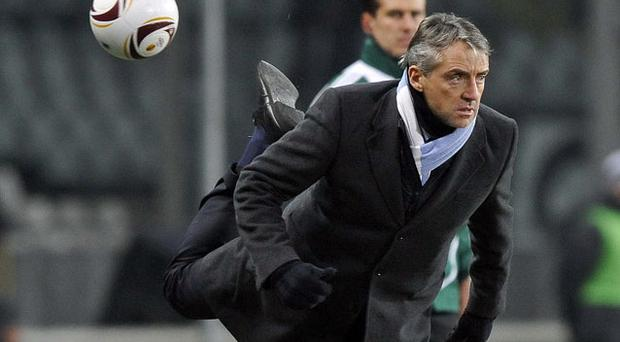 Manchester City manager Roberto Mancini attempts to acrobatically flick the ball back into play during their Europa League game in Turin last night. Photo: Reuters
