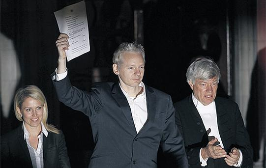 WikiLeaks founder Julian Assange celebrates as he emerges to speak to the media on the steps of the High Court in London yesterday