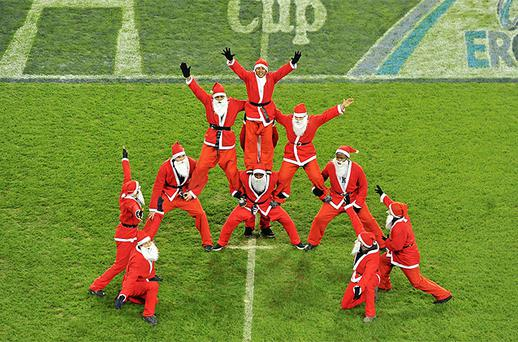 Performance artists dressed as Santa Claus make a human pyramid during the pre-match entertainment before the game. Photo: Sportsfile