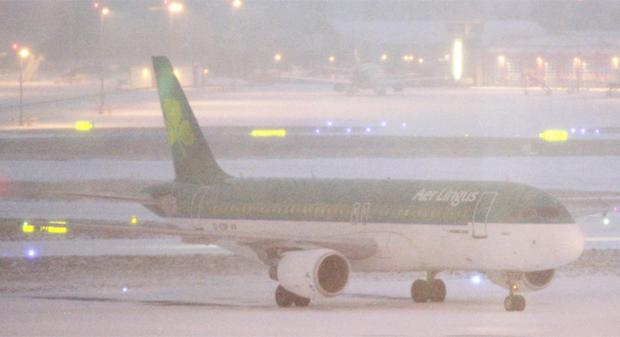 An Aer Lingus aircraft taxis through the snow on the runway at Dublin airport. Photo: PA