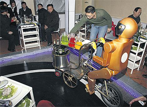 A customer collects a drink from a robot waiter cycling around a restaurant in Jinan in eastern China's Shandong province