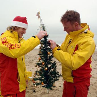 Lifeguards John Simmonds and Justin White get ready for Christmas at Boscombe beach in Dorset