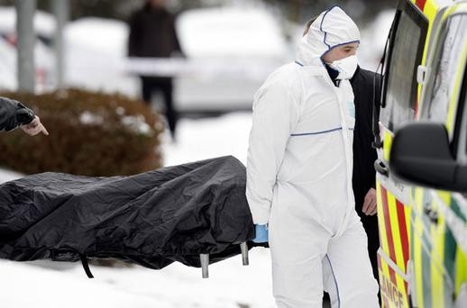 A woman's body is removed from an apartment block in Clonsilla, Dublin, yesterday. Photo: STEVE HUMPHREYS