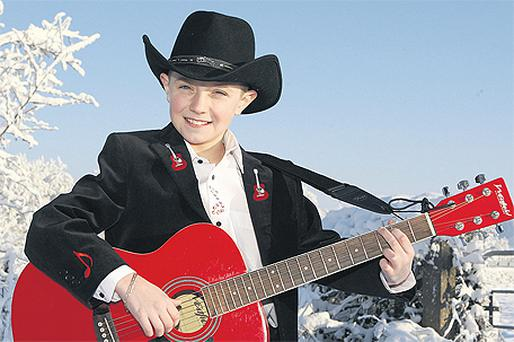 Up and coming young country star Simon Peters poses with his guitar in the snow