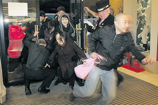 Eager shoppers rush into Brown Thomas in Dublin yesterday for the start of its winter sale