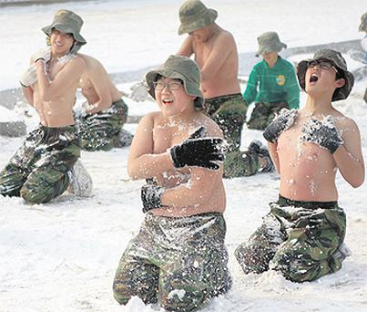 Elementary and middle school students rub their bodies with snow during a military camp, conducted by retired Korean marines corps, in Ansan, about 40 km southwest of Seoul yesterday. The camp is designed to strengthen the students' mental and physical endurance