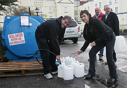 Brendan Bannigan and Francine Shelly filling containers at a water tanker beside the Grand Hotel, Malahide, Dublin
