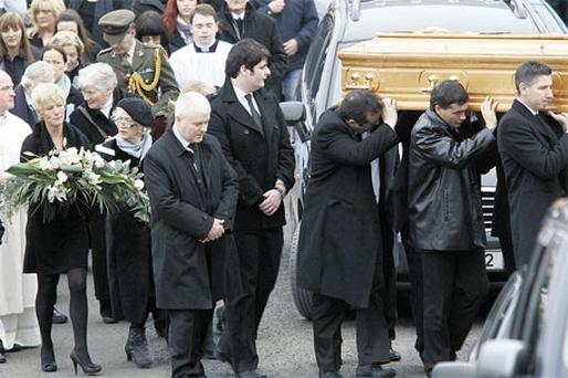 Roisin's coffin is followed by sister Eileen (carrying flowers, left) and mother Catherine. Photo: Declan Doherty