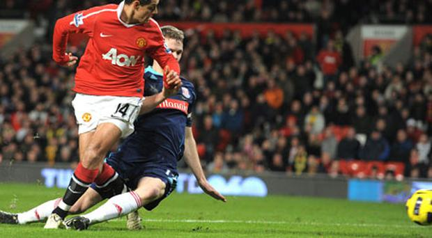 Manchester United's Javier Hernandez flicks the ball past Stoke City's Ryan Shawcross to score during the Premier League clash at Old Trafford last night - United won 2-1 to go three points clear at the top of the table. Photo: Getty Images
