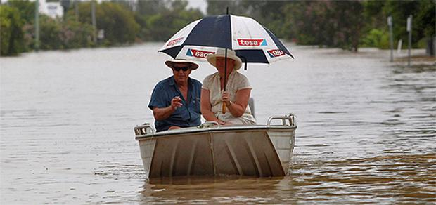 A couple navigates through floodwaters at Depot Hill in Rockhampton, Queensland. Photo: Reuters
