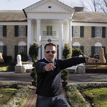 Chilean miner Edison Pena strikes a Presley pose outside Graceland, Presley's home, in Memphis, US (AP)