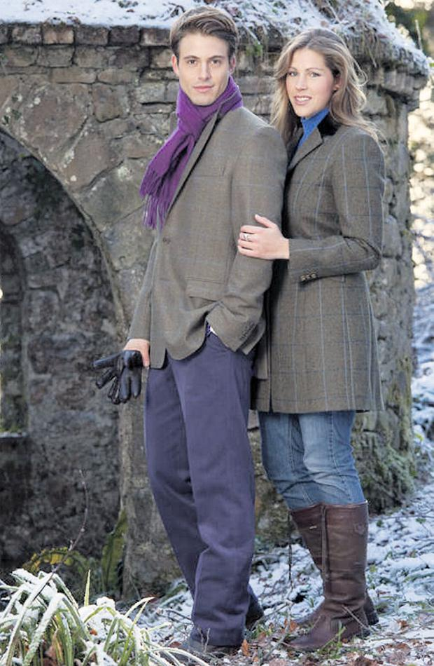 He wears: country-check jacket, €375; blue corduroy trousers, €85, purple scarf, €30, all by Magee; boots, model's own. She wears: Portnoo three-quarter-length jacket, €325, Magee; polo neck, jeans and boots, model's own