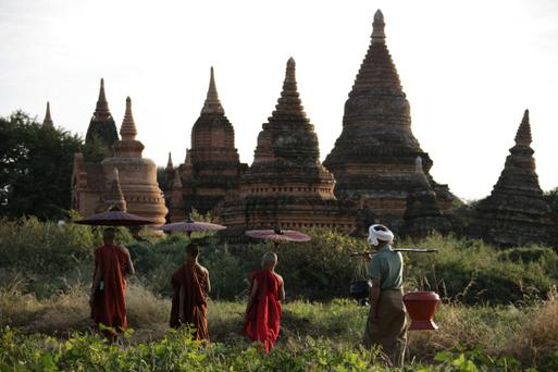 BAGAN, BURMA - JANUARY 18: Monks with traditional parasols walking through the historical temple area of Bagan on Jan 18, 2007 in Bagan, Burma.Once the capital of the first Myanmar Kingdom, Bagan has about 4000 sacred stupas and buddhist monuments built between the 10th and 14th centuries AD. In 2002 Bagan was nominated as UNESCO World Heritage. (Photo by EyesWideOpen/Getty Images)