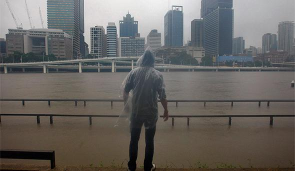 A man looks at the rising Brisbane River in the city's central district. Photo: Reuters