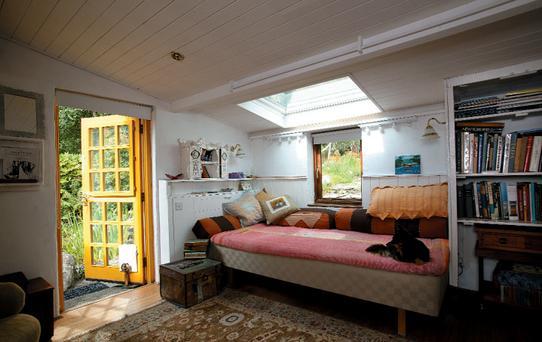 Poppy's dog, Bee, enjoys Pauline's bedroom which is decorated with kilim-covered cushions which the artist has picked up on her travels