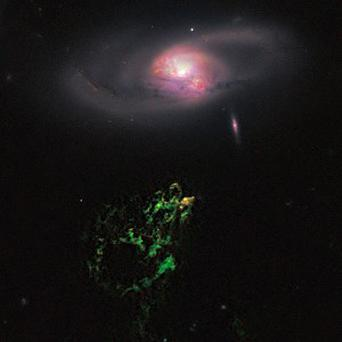 An unusual, ghostly green blob of gas appears to float near a normal-looking spiral galaxy (AP)
