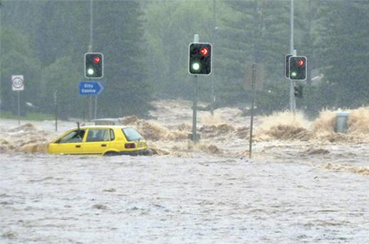 A passenger in a car waves for assistance as a flash flood sweeps across an intersection in Toowoomba, 105 km west of Brisbane. Photo: Reuters
