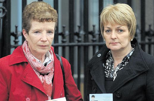 Kay Keane and Magdalene Farren hold pictures of their daughters Eileen and Sinead outside the Dail yesterday