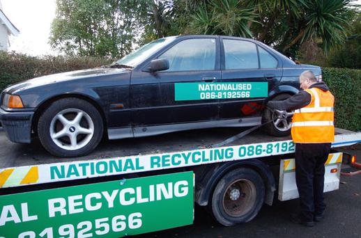 A 92-D, 3-Series BMW formerly belonging to ex-Anglo boss Sean FitzPatrick is collected by its new owners, National Recycling, outside his house in Greystones, Co Wicklow, yesterday. Photo: DAMIEN EAGERS