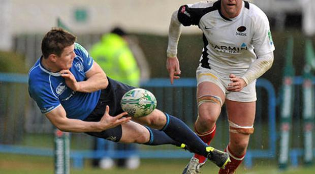 Leinster's Brian O'Driscoll keeps the ball in play as Ernst Joubert of Saracens looks on at the RDS on Saturday. Photo: Brendan Moran / Sportsfile