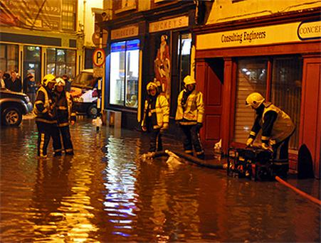 Firefighters pump water from Bridge Street in Bandon, Co Cork, early yesterday morning
