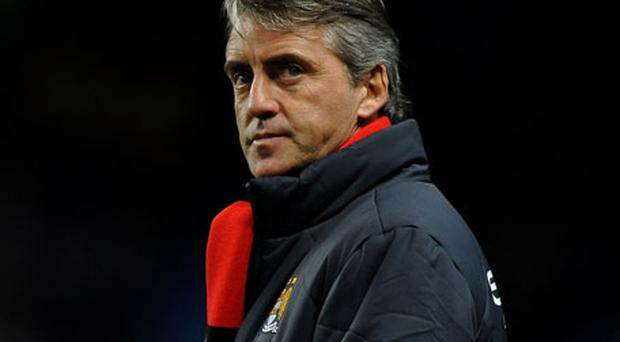 Manchester City manager Roberto Mancini wears a black and red scarf as a tribute to former Manchester City player Neil Young who is currently battling cancer. Young wrote his name into City folklore by scoring the goal which won the 1969 final against Leicester at Wembley. Photo: Getty Images