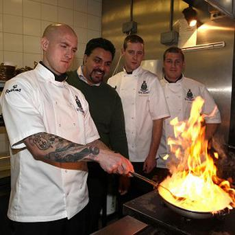 Chef Arfan Razaic (second left) instructs Royal Marines Ian Dixon, Ryan Murphy and Michael Anderson in curry cookery