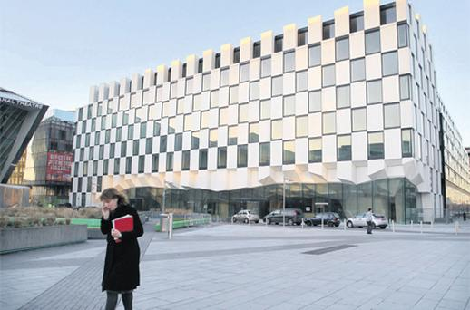 A woman walks by the almost completed five-star hotel at Grand Canal quarter in Dublin yesterday