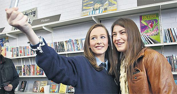 Second-year student Lauren McCoy takes a picture with Katie Taylor as the boxing star opened new library facilities at St Kevin's College in Crumlin, Dublin, yesterday. Photo: Frank McGrath