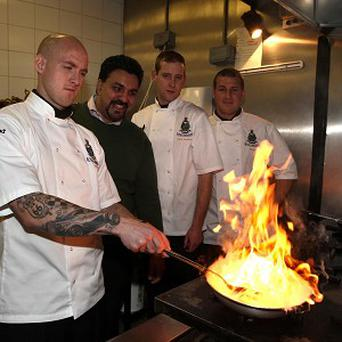 Cpl Ian Dixon (left), Marine Ryan Murphy (second right) and Cpl Michael Anderson (right) are taught Indian cooking by chef Arfan Razak