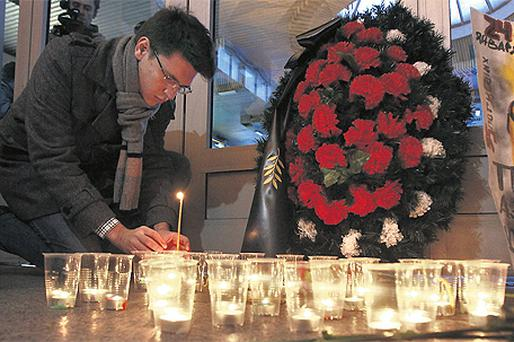 A man lights a candle at the Moskovsky railway station in St Petersburg, Russia, yesterday, to commemorate the victims of a suicide bombing at Domodedovo airport