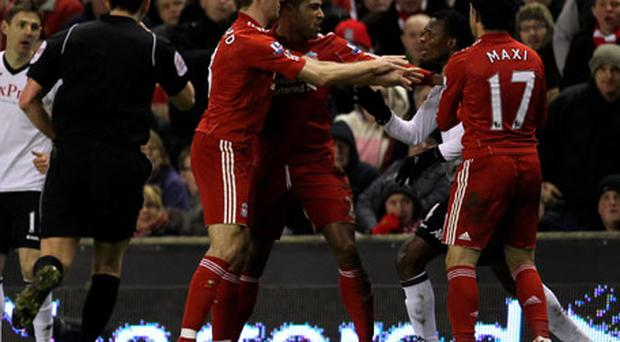 John Pantsil of Fulham clashes with Steven Gerrard and Glen Johnson of Liverpool at Anfield last night. Photo: Getty Images
