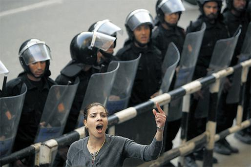 Mariam Solayman, a member of an Egyptian activist group, shouts anti-government slogans in front of a police cordon during a demonstration in central Cairo yesterday