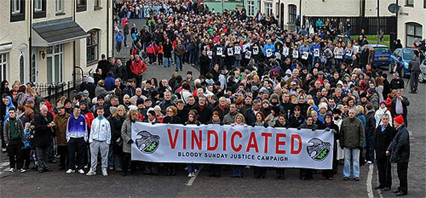 People hold up a banner during yesterday's parade in Derry marking the anniversary of Bloody Sunday