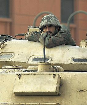 An Egyptian soldier in his tank at Tahrir Square in Cairo yesterday, as protesters began digging in for a long fight in their demand for the resignation of President Hosni Mubarak
