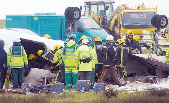Fire crew and paramedics working at the scene of the Manx2 air crash at Cork Airport yesterday morning. Photo: Daragh McSweeney / Provision